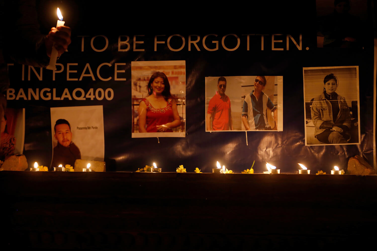 People attend a candlelight vigil in remembrance of the 49 people who died in Monday's US-Bangla plane crash at Maitighar on Tuesday.