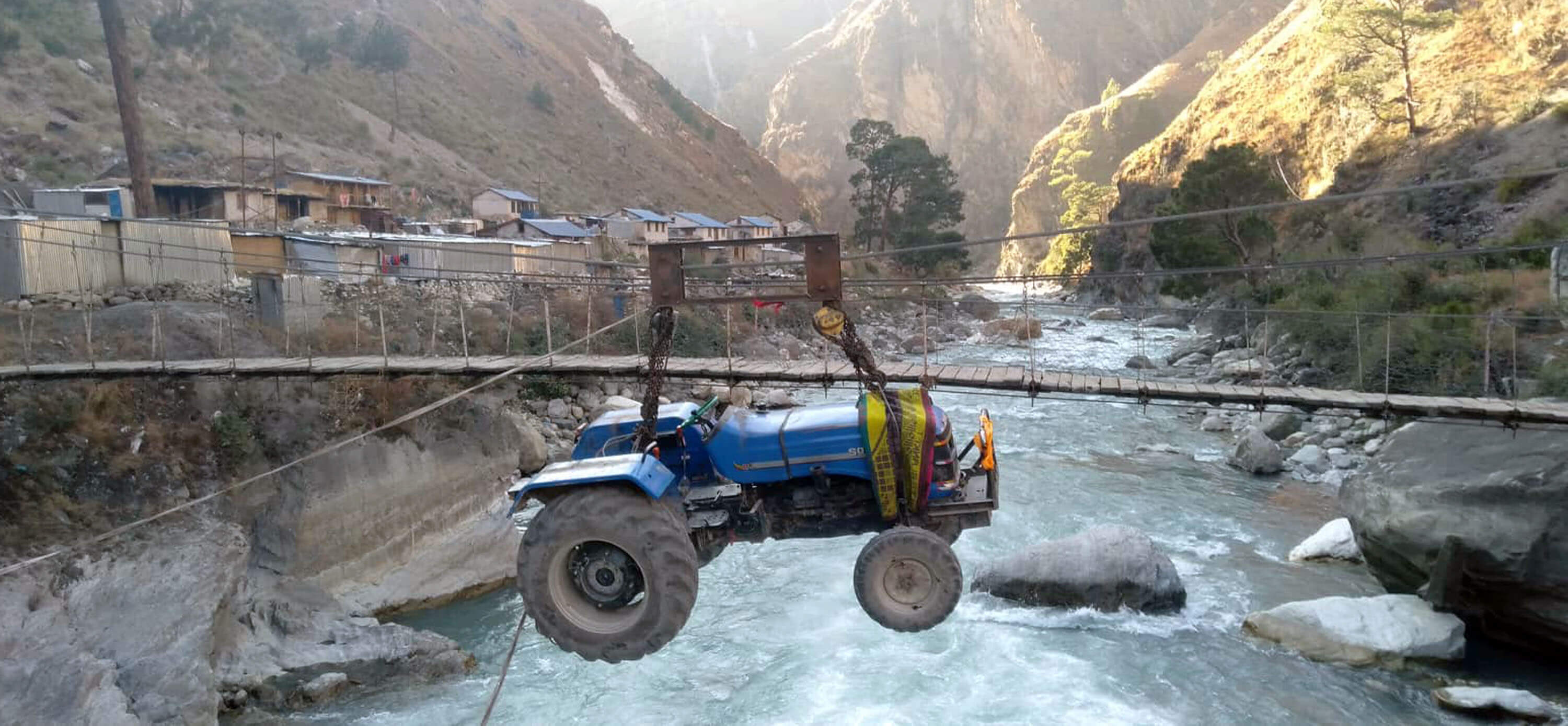 A manual pulley is used to transport part of a tractor over the Bheri river in Khadang, Tripurakot of Dolpa, a remote mountain district with very few roads and bridges.