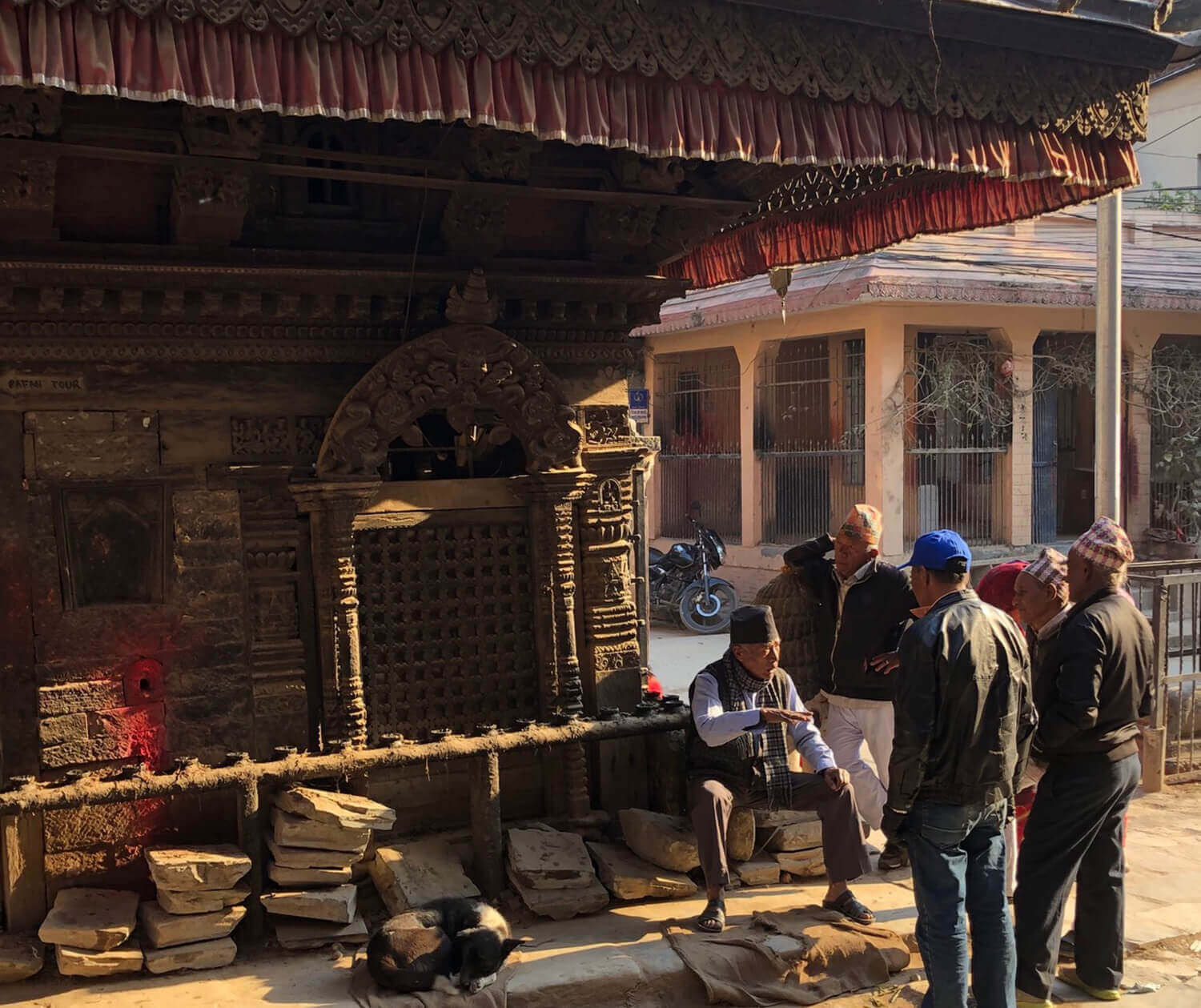 Patan neighbours meet up at a temple as a pale winter sun comes out after days of overcast skies and rain in Kathmandu Valley.