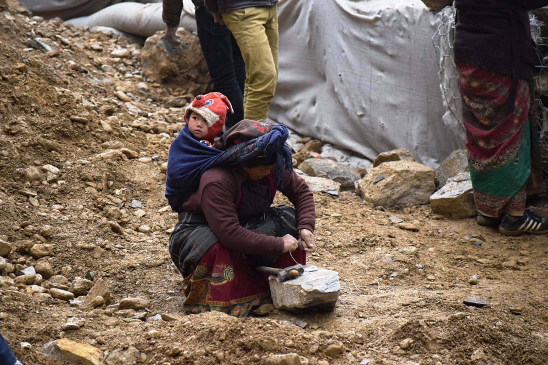 A woman labour from Rolpa working on Beni-Jomsom-Korala road project breaks stone as she carries her infant baby on her back in Mustang, Kobang on Tuesday.