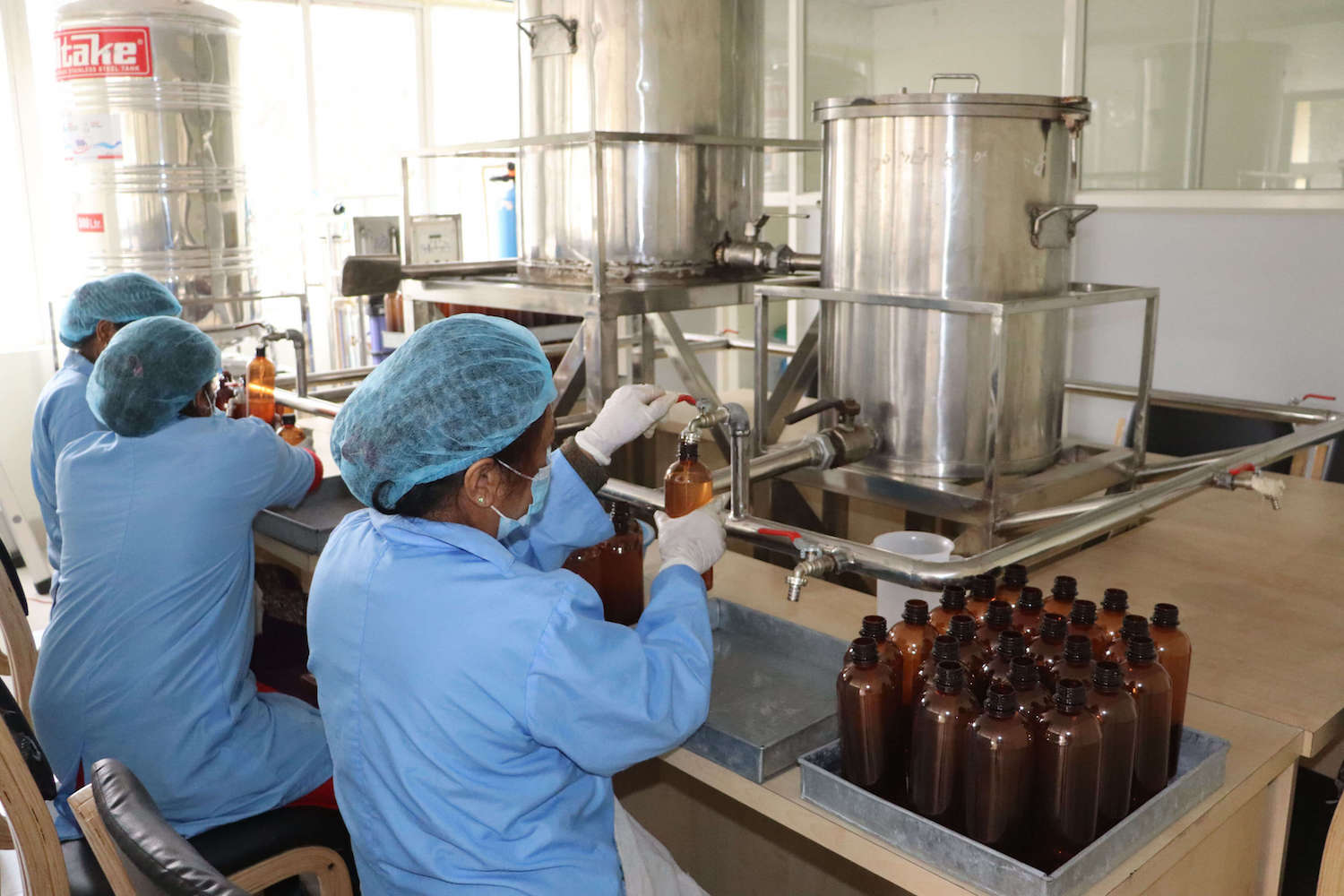 Staff at the Herbs Production & Processing Co. Ltd. in Jadibuti work on manufacturing and packaging sanitiser for  the market.