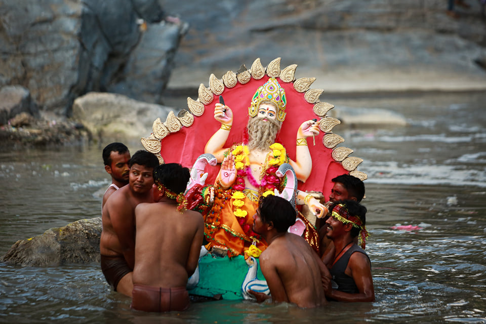 Devotees immerse the idol of lord Biswakarma, the Hindu deity of architecture and engineering, in the Bagmati river in Kathmandu.