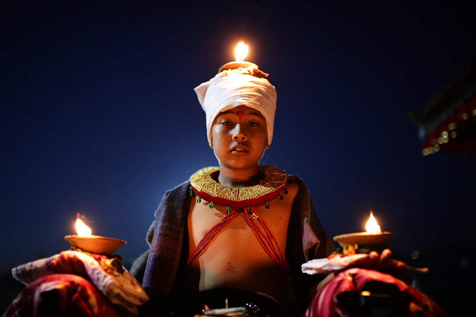 A young devotee holds burning oil lamps on his head and palms while offering prayers as part of a ritual on the tenth day of the Dasain festival in Bhaktapur's Branayeni temple.